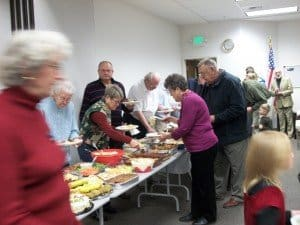 People in lines on both sides of a potluck table covered with food