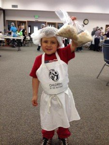 A child holds up bags of food while wearing a Children of the Nations apron.