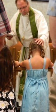 Photo of Pastor Ken blessing a young girl with other people kneeling at the communion rail