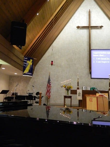 Photo of the sanctuary with cross, altar and piano