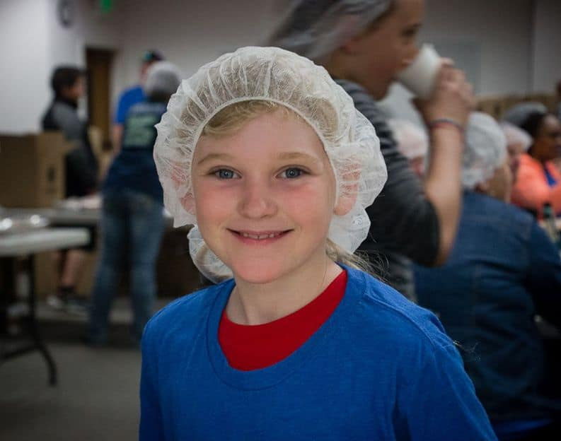Girl in blue wearing hair net with a smile
