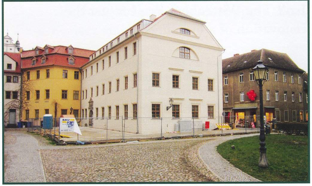 Photo of a white building with at least 3 floors