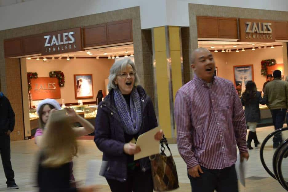 Photo of a man and a woman walking in the mall singing
