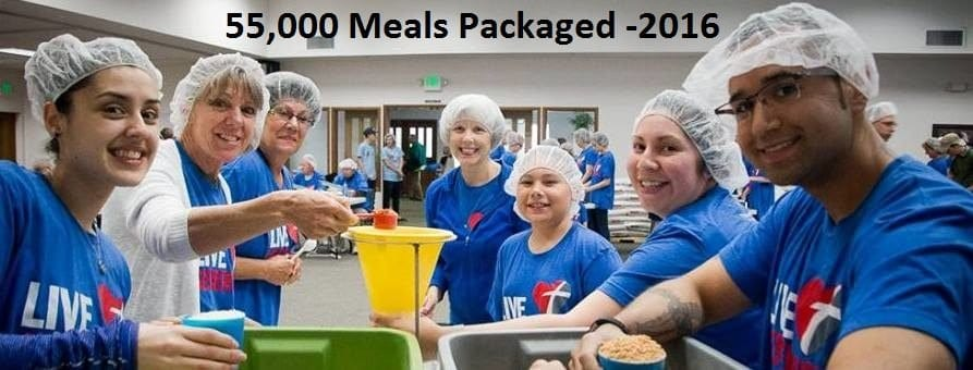 "People around a table holding measuring cups of ingredients with a yellow funnel in the center and the words ""55,000 Meals Packaged -2016"""