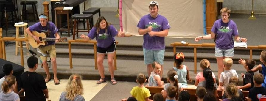 4 Adults with purple tee shirts at the front of the sanctuary with children in the pews