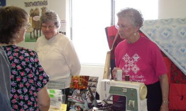 Ladies standing on both sides of a table with a sewing machine and other items