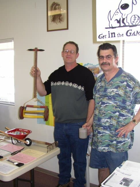 Two men standing behind a table with a lawn mower and a wheelbarrow