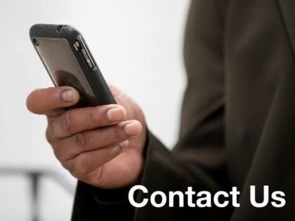 """Photo of a cell phone in a man's hand and the words """"Contact Us"""""""