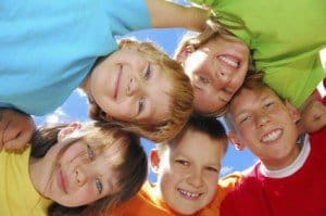 Photo of five children's faces with their heads together in the center of the picture
