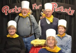 "Five people wearing chef hats around a large bowl of pasta with a banner displaying the words ""Pasta for Parents"" behind them."
