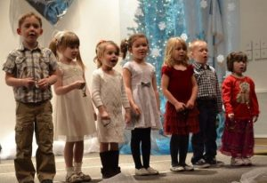 7 preschool children on stage singing Christmas songs with a Christmas tree in the background.