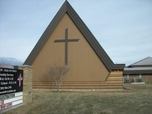 A-frame church building with cross on south side of the church.