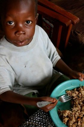 Child using a fork to eat food from a bowl