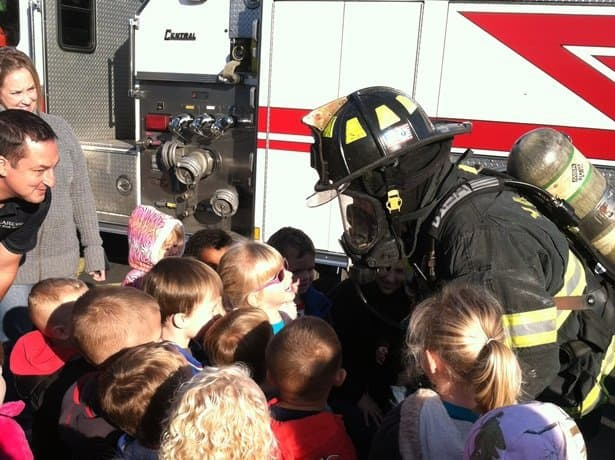 A Firefighter in his air mask showing all the children.