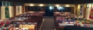 Photo of quilts arrayed on the pews waiting to be blessed in the Sanctuary.