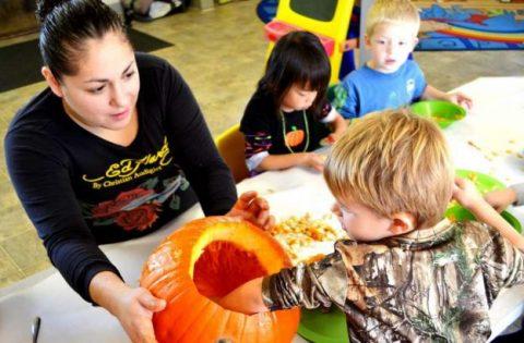Teacher with chidren's hand inside the pumpkin.