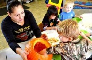 Photo of a teacher holding a pumpkin with child's hand inside the pumpkin.