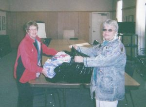Two women opening a bag on a table displaying a quilt.