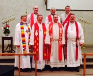 Photo of seven Visiting Pastors with Pastor Ken in the front with all wearing white robes standing in front of the Sanctuary.