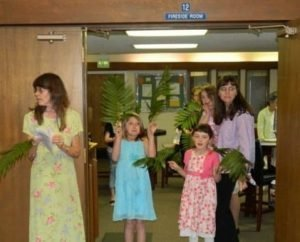 Photo from the Narthex of the Fireside Room entrance including young ladies with palm branches in their hands