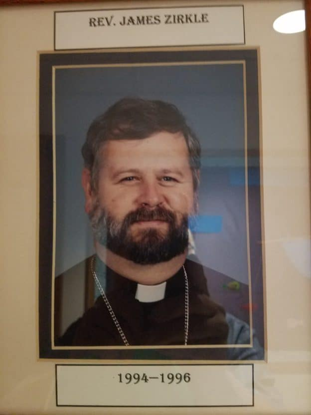 Photo of a framed picture of a man with a beard and mustache and wearing a pastor's collar