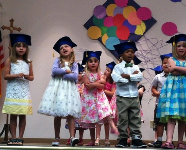 Photo of Preschoolers on Stage Wearing mortar boards.