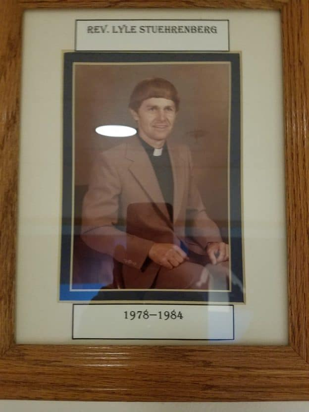Photo of a framed picture of a man seated wearing a jacket and a pastor's collar