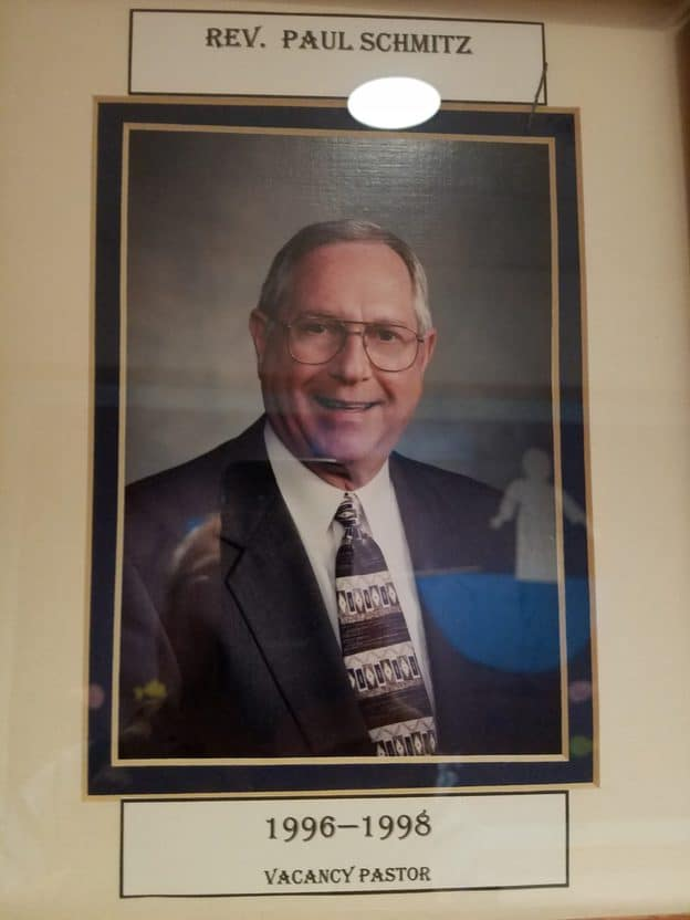 Photo of a framed picture of a man with glasses wearing a jacket and tie