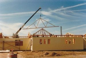 Photo of a crane lifing roof trusses into place during construction of the west wing