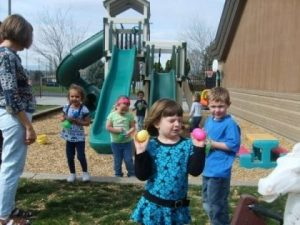Photo of children on playground, a girl with big Easter eggs in each hand with slides and other children in the background.