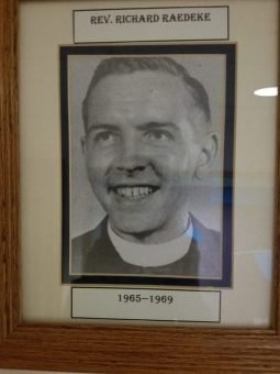 Photo of a framed portrait of a smiling man with a pastor's collar