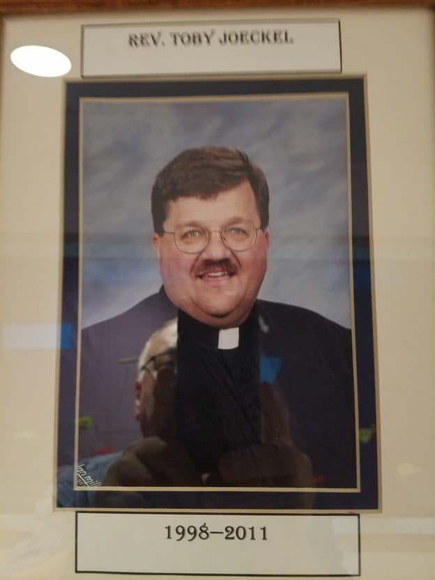Photo of a framed picture of a man with a mustache dressed in black with a pastor's collar