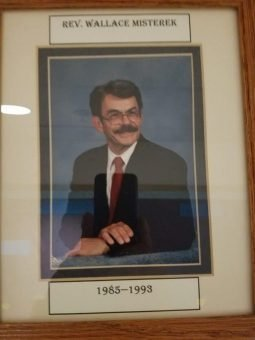 Photo of a framed picture of a man with glasses and a mustache wearing a jacket and a tie