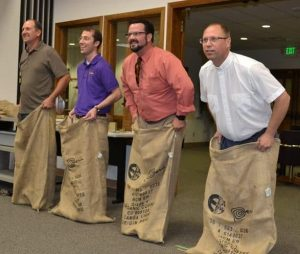 Photo of Pastor Ken and 3 dads lined up for gunny sack race