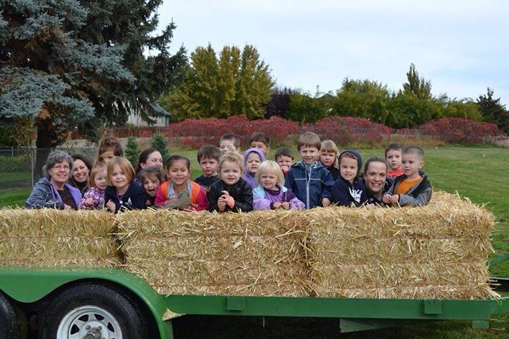 About 20 children inside walls made of straw bales on a wagon