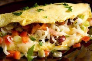 Picture of an omelet close-up showing a variety of ingredients inside the omelet