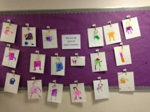 "Photo of a display: 18 ""Mat Man"" Self Portraits hang from string with closepins in front of a purple background."