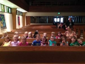 Photo of a Preschool class with their teacher seated in the pews ready for Chapel.