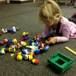"Photo of a girl lying on the carpet and playing with small plastic figures during ""Center Play."""