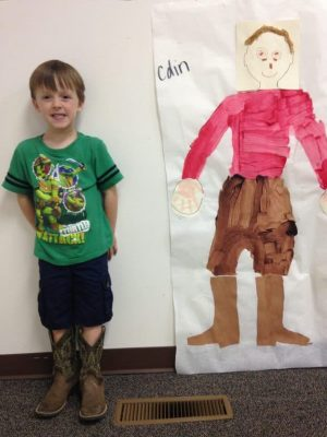 Photo of a boy standing beside his full size picture of himself, a self portrait on butcher paper.