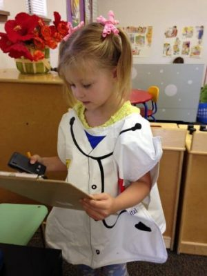 A preschool girl uses doctor's gown and play instruments