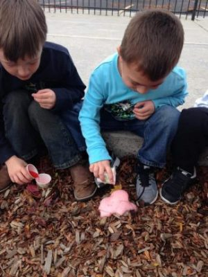 """Two boys are sitting on a curb making their tiny volcanoes """"erupt."""""""