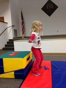 Photo of a girl jumping on mats.