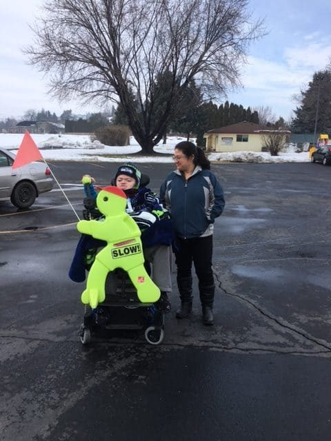 "A warmly dressed lady standing by a Boy in a wheelchair holding a fluorescent yellow sign shaped like a child with a red flag and the word ""SLOW"" in the parking lot with a snowy background"