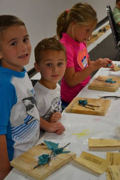 Children at a table with their art projects spread out