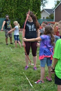 Staff adults lead children shooting bows and arrows