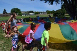 Large group of children holding onto a multicolored parachute