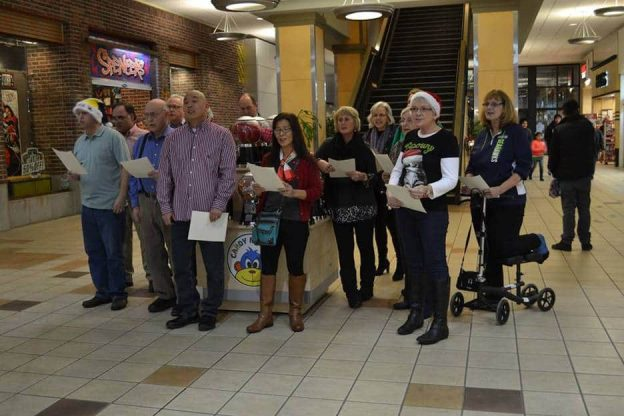 Photo of about a dozen people standing and singing in the mall.