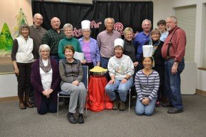More than a dozen adult helpers pose around a large bowl of pasta.