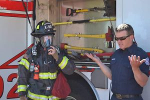 Photo of two firefighters demonstrate their breathing apparatus.